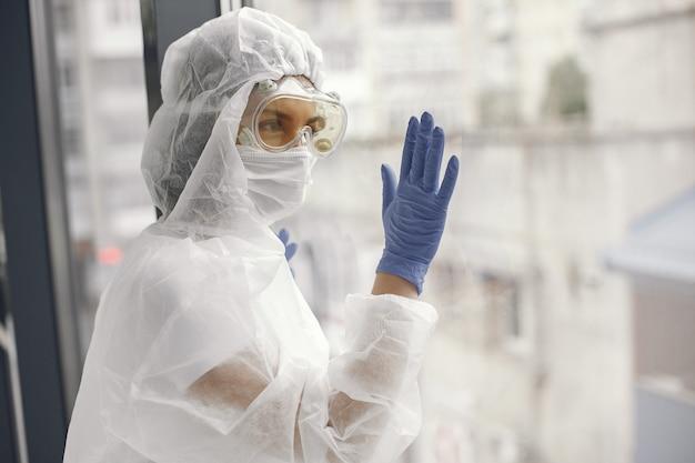 コロナウイルスパンデミックコビッド-2019。防護服、グーグル、手袋、マスク。