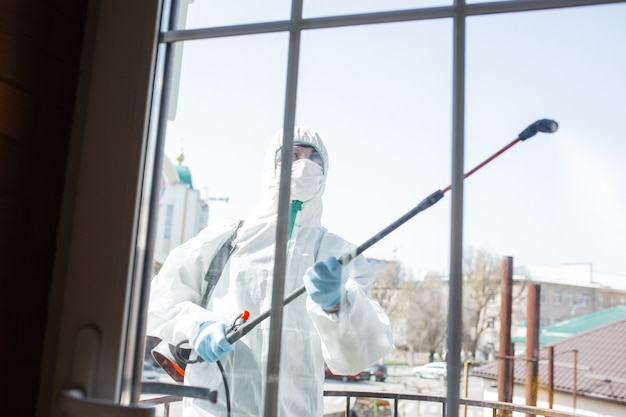 Coronavirus pandemic. a disinfectant in a protective suit and mask sprays disinfectants in the room.