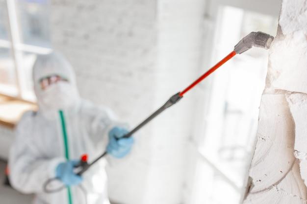 Pandemia di coronavirus. un disinfettante in tuta protettiva e maschera spruzza disinfettanti nella stanza.