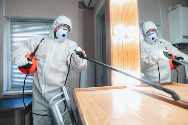코로나 바이러스 감염병 세계적 유행. 보호 복의 소독기 및 마스크는 집이나 사무실의 소독제를 스프레이합니다.