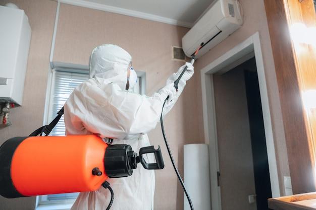 コロナウイルスパンデミック。保護スーツを着た消毒器とマスクが家またはオフィスに消毒剤をスプレーする