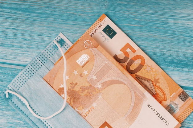 Coronavirus pandemic in europe. flat lay of face mask and euro banknotes
