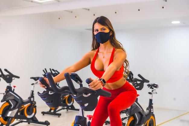 Коронавирус пандемия. девушка тренируется на статических велосипедах с маской для лица, тренажерные залы с ограниченной вместимостью, социальная дистанция и новый стандарт