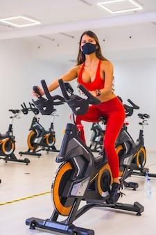 코로나 바이러스 감염병 세계적 유행. 안면 마스크가있는 정적 자전거, 용량이 감소 된 체육관, 사회적 거리 및 새로운 정상으로 훈련하는 소녀