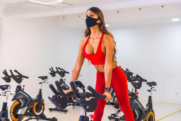 Коронавирус пандемия. тренировка девочек на велотренажерах, тренажерные залы с ограниченной вместимостью, социальная дистанция и новый стандарт