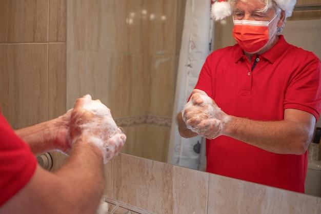 Профилактика пандемии коронавируса. мужчина моет руки дома в хирургической маске из-за коронавируса, с рождественской шляпой на голове. сосредоточьтесь на пене в зеркале