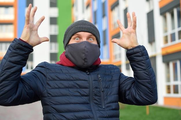 コロナウイルスパニック。市の顔にマスクをした男が、コロナウイルスに関する悪い知らせに慌てています。