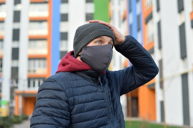 Coronavirus panic. man with a mask on his face in the city panic over the bad news concerning corona virus
