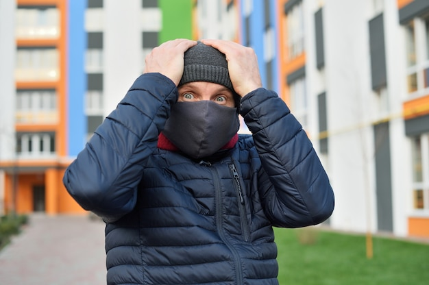 Coronavirus panic. man with a mask on his face in the city panic over the bad news concerning coronavirus