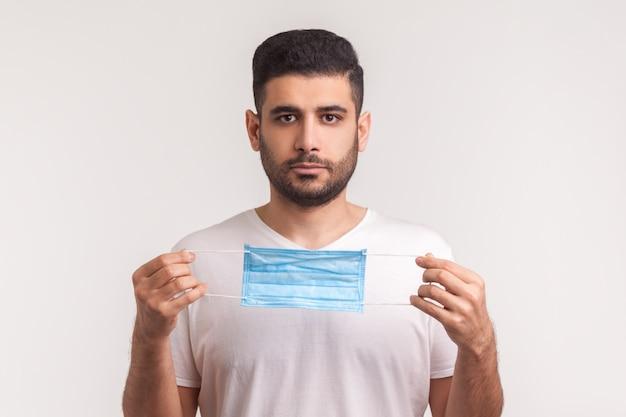 コロナウイルス予防意識。感染から保護するために医療マスクを保持している男の肖像画