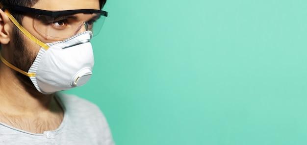 코로나 바이러스 예방. 독감에 대 한 의료 호흡 마스크, 아쿠아 menthe 색상의 배경에 안전 고글을 착용하는 젊은 남자의 클로즈업 스튜디오 초상화.