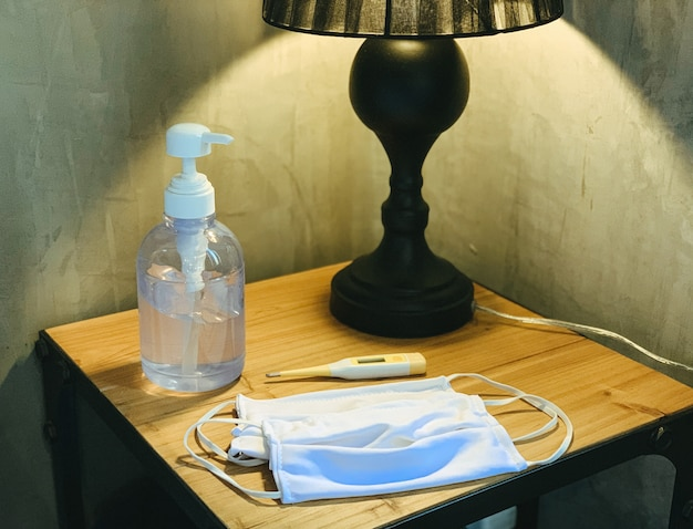 Coronavirus prevention medical surgical masks, hand sanitizer gel and thermometer on wooden table. personal hygiene concept
