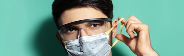 코로나 바이러스 예방. 아쿠아 menthe 색상의 배경에 안전 고글을 착용하는 의료 호흡 마스크에 젊은 남자의 파노라마 초상화.
