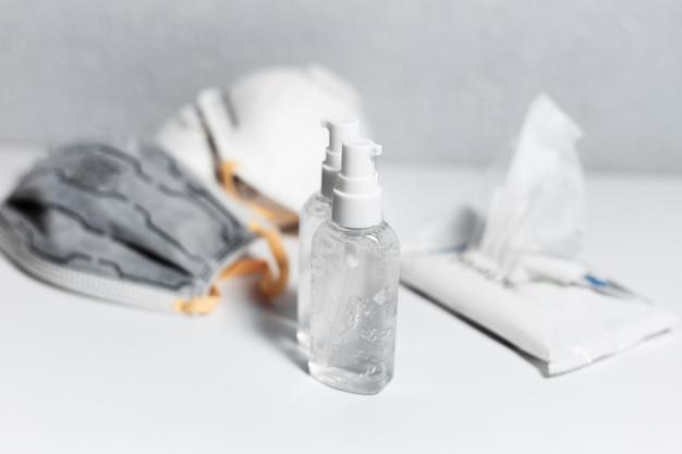 코로나 바이러스 예방. 의료 독감 마스크 근처에 소독제 살균 젤 두 병과 흰색 테이블에 젖은 물티슈. 평면도.