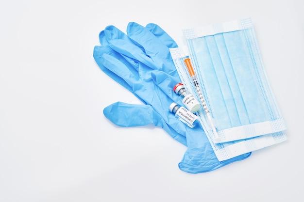 Вакцина для профилактики коронавируса, медицинская защитная маска и одноразовые перчатки, изолированные на белом фоне