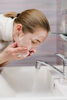 Coronavirus prevention. wash face with antibacterial soap and running water in sink. washing face. epidemic covid-19. coronavirus prevention body hygiene. flu disease.