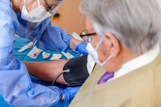 コロナウイルスで保護された看護師が老人の血圧計のカフを取ります