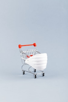 Coronavirus protection concept. mini grocery cart and medical face shield. protect yourself with mask from coronavirus while shopping