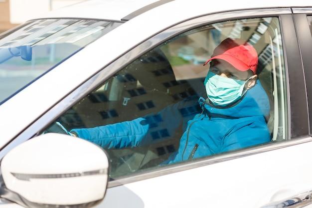코로나바이러스 보호입니다.보호 마스크와 장갑을 낀 택시 운전사. 개념: 중지: covid-19