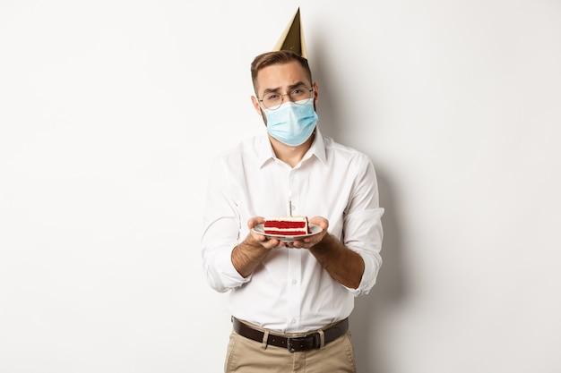 코로나 바이러스, 격리 및 휴일. 슬픈 남자는 생일 케이크, 얼굴 마스크를 착용하고 불평, 흰색 배경 위에 서서 촛불을 날릴 수 없습니다.