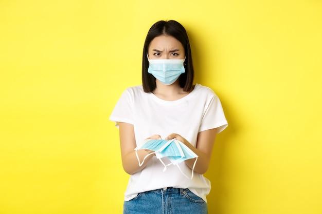 コロナウイルス、検疫および医学の概念。あなたに屋内で医療マスクを与える怒っているアジアの女の子、眉をひそめている、黄色の背景の上に立っている