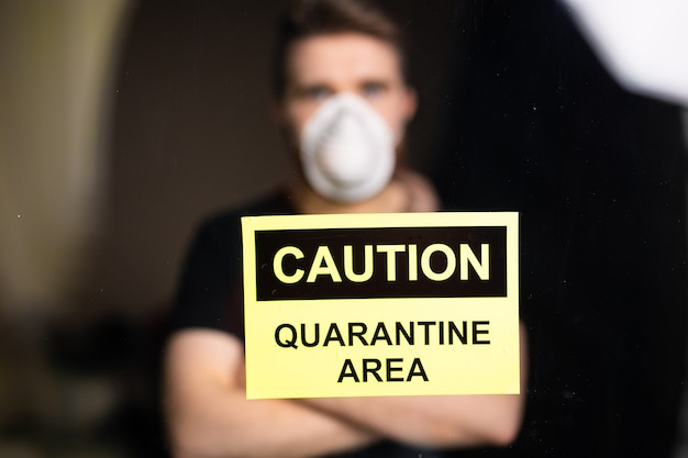 コロナウイルス、検疫およびパンデミックの概念。窓越しに見ているコロナウイルスの悲しくて病人