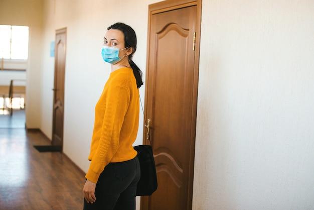 Коронавирус карантин. закрытие офиса во время эпидемии коронавируса. женщина с маской собирается домой.