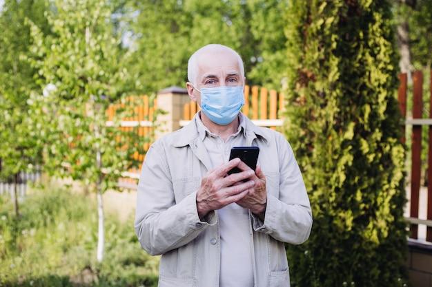 コロナウイルスの検疫、コロナウイルス、医療用フェイスマスクを持つ男が電話を使用してニュースを検索します。大気汚染