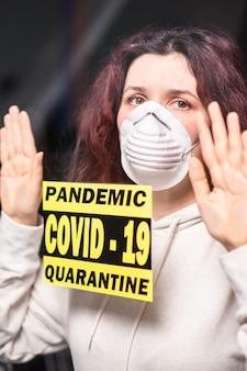 Коронавирус, карантин, covid-19 и концепция пандемии. грустная и больная женщина с вирусом короны смотрит в окно