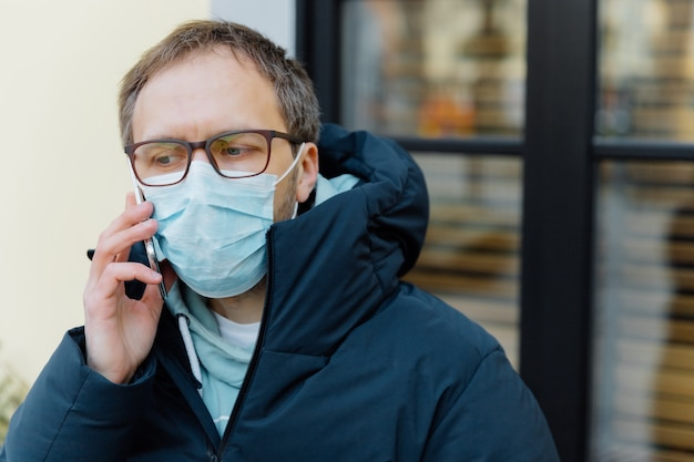 Coronavirus quarantine. sad puzzled man in panic because of epidemic disease, covers face with medical mask, wears spectacles, keeps mobile phone near ear, consults doctor on distance, stands outdoor