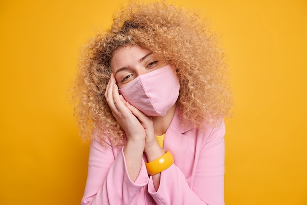 Coronavirus and quarantine time concept. beautiful young woman with bushy curly hair wears protective mask at public place to prevent virus dressed in formal clothes isolated over yellow wall