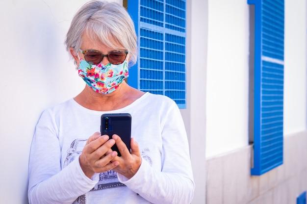 Коронавирус. старшая женщина в хирургической маске пишет сообщение с помощью смартфона. стоя у белой стены с помощью беспроводной технологии. старые люди и новая молодая концепция