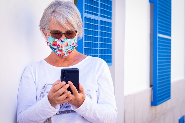 Coronavirus. senior woman wearing surgical mask writes a message with smartphone. standing against a white wall using wireless technology. old people and new young concept