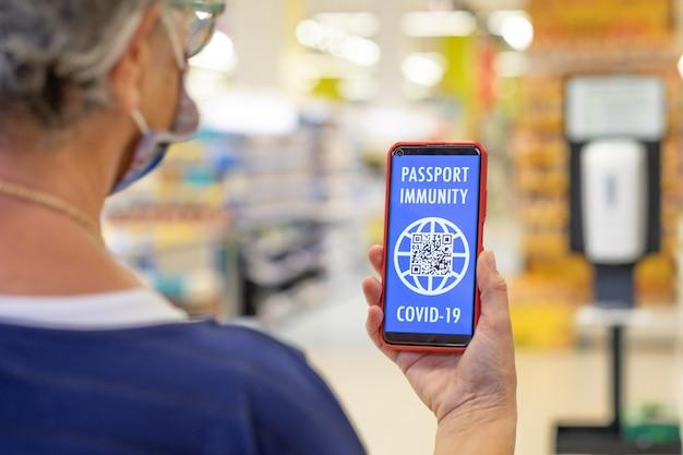 코로나 바이러스. 얼굴 마스크를 쓴 노인 여성이 그린 카드, 예방 접종 여권을 들고 쇼핑몰에 입장