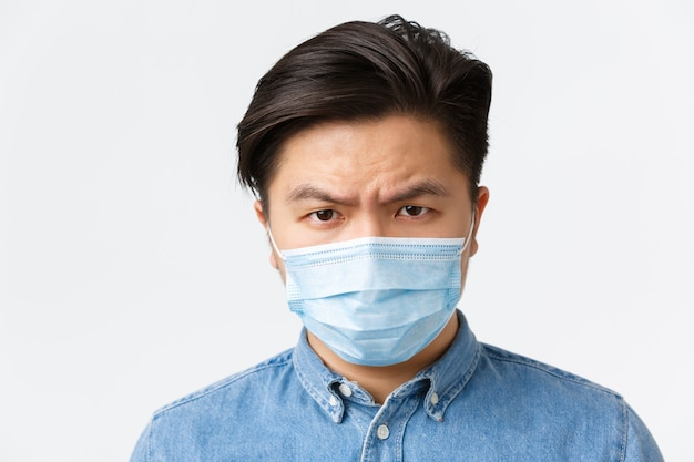 코로나바이러스, 사회적 거리 및 생활 방식 개념. 코비드-19 동안 보호 조치를 사용하지 않는 사람을 보고 실망한 의료 마스크를 쓴 화나고 화난 아시아 남성의 클로즈업.