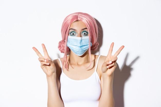 コロナウイルス、社会的距離とライフスタイルの概念。医療マスクとピンクのかつらでかわいいパーティーの女の子のクローズアップ、興奮しているように見える平和の兆候、白い背景を示しています。