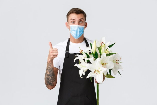 コロナウイルス、covid-19パンデミックコンセプトの間の社会的距離ビジネス。興奮した感動のセールスマン、フラワーショップの花屋は医療用マスクを着用し、親指を立てて、顧客のために素晴らしい花束を作りました