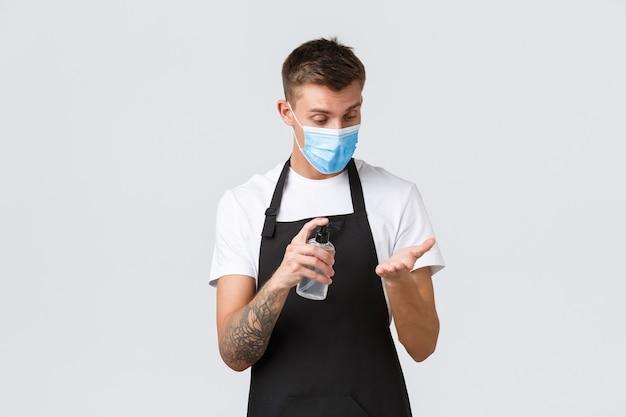 Coronavirus, distanza sociale in caffè e ristoranti, affari durante il concetto di pandemia. barista, impiegato del negozio che disinfetta le mani con disinfettante per le mani, cameriere che lavora in maschera medica
