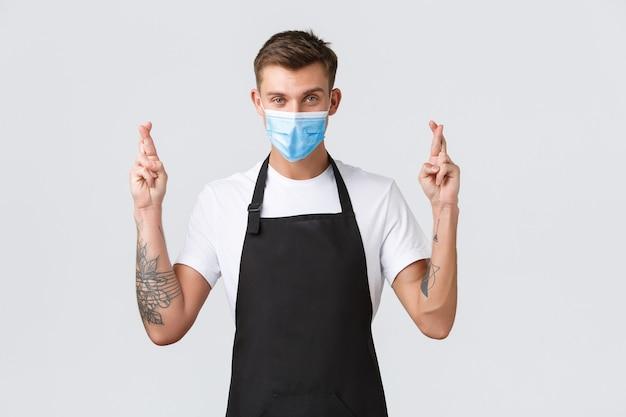 Coronavirus, distanza sociale in caffè e ristoranti, affari durante il concetto di pandemia. barista fiducioso e fiducioso, venditore in maschera medica incrocia le dita buona fortuna, esprimendo desideri o implorando