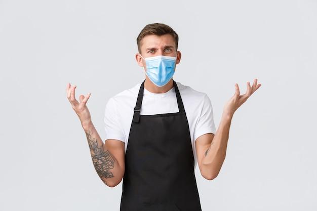 Coronavirus, distanza sociale in caffè e ristoranti, affari durante il concetto di pandemia. barista lamentoso frustrato in maschera medica che stringe la mano e li solleva delusi, litigando