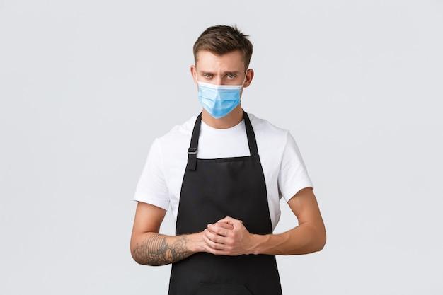 Coronavirus, distanza sociale in caffè e ristoranti, affari durante il concetto di pandemia. responsabile del caffè serio e determinato che ascolta l'ospite, indossa una maschera medica per prevenire la diffusione del virus