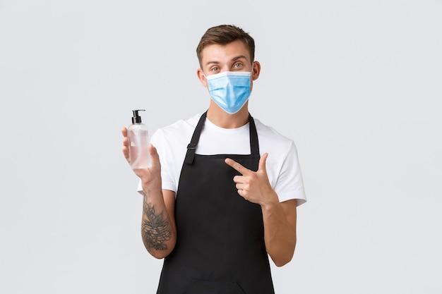 Coronavirus, distanza sociale in caffè e ristoranti, affari durante il concetto di pandemia. il cameriere o il barista spiegano l'importanza di indossare la mascherina e usare il disinfettante per le mani per disinfettare