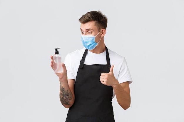코로나바이러스, 카페와 레스토랑에서의 사회적 거리, 전염병 개념 동안 비즈니스. 식료품점, 바리스타 또는 웨이터의 쾌활한 세일즈맨은 소독을 위해 엄지손가락을 치켜들고 손 소독제를 보여줍니다.