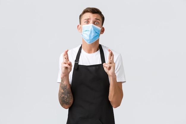 코로나바이러스, 카페와 레스토랑에서의 사회적 거리, 전염병 개념 동안 비즈니스. 절망적이고 걱정스러운 판매원, 가게 주인은 행운을 빕니다, 의료용 마스크를 쓰고 기도합니다