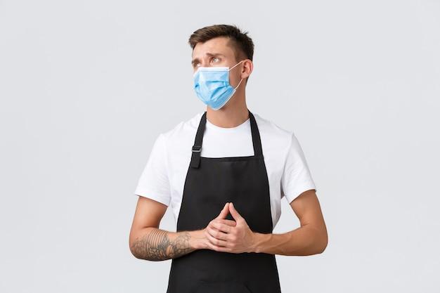 코로나바이러스, 카페와 레스토랑에서의 사회적 거리, 전염병 개념 동안 비즈니스. 실망하고 슬픈 바리스타, 앞치마를 입은 세일즈맨과 의료용 마스크가 불쾌하고 화가 난 것처럼 보입니다.