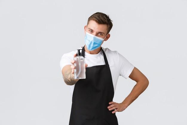 코로나바이러스, 카페와 레스토랑에서의 사회적 거리, 전염병 개념 동안 비즈니스. 소독용 손 소독제를 제공하는 의료용 마스크를 쓴 친절한 미소 짓는 웨이터, 바리스타 또는 판매원