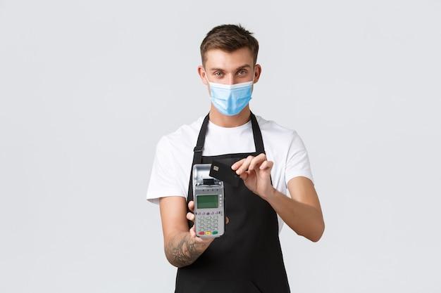 팬데믹 컨셉의 잘생긴 남자 동안 카페와 레스토랑 비즈니스에서 코로나바이러스 사회적 거리두기...