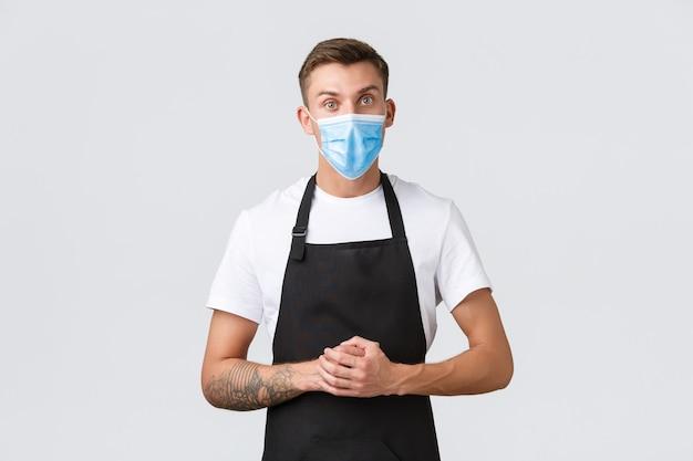 코로나바이러스, 카페와 레스토랑에서의 사회적 거리, 전염병 개념 동안 비즈니스. 의료용 마스크를 쓴 진지한 바리스타, 카운터 너머로 고객의 말을 듣고 있는 세일즈맨, 흰색 배경