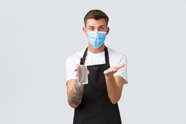 코로나바이러스, 카페와 레스토랑에서의 사회적 거리, 전염병 개념 동안 비즈니스. 웨이터 또는 바리스타가 마스크 착용의 중요성과 소독을 위한 손 소독제 사용의 중요성을 설명합니다.