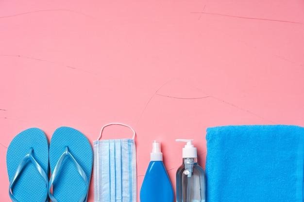 コロナウイルスの夏のアクセサリー。青いタオル、ビーチサンダル、日焼け止め、保護マスク、ピンクの背景に手指消毒剤